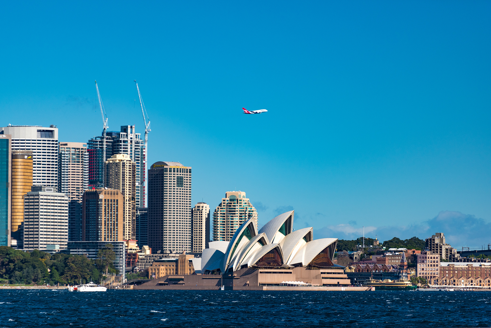 Sydney Australia - July 23 2016: Sydney Opera House and Central Business District with Qantas plane against blue sky on the background. Qantas is Australia's largest airline and the flag carrier